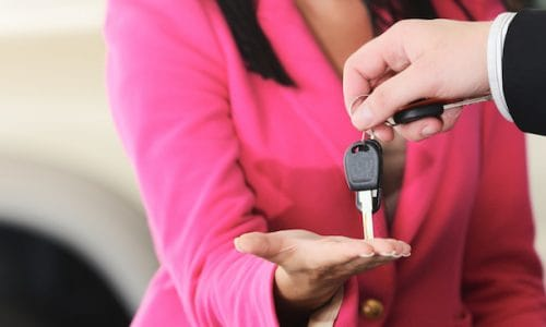 Man handing woman automobile keys for the new car